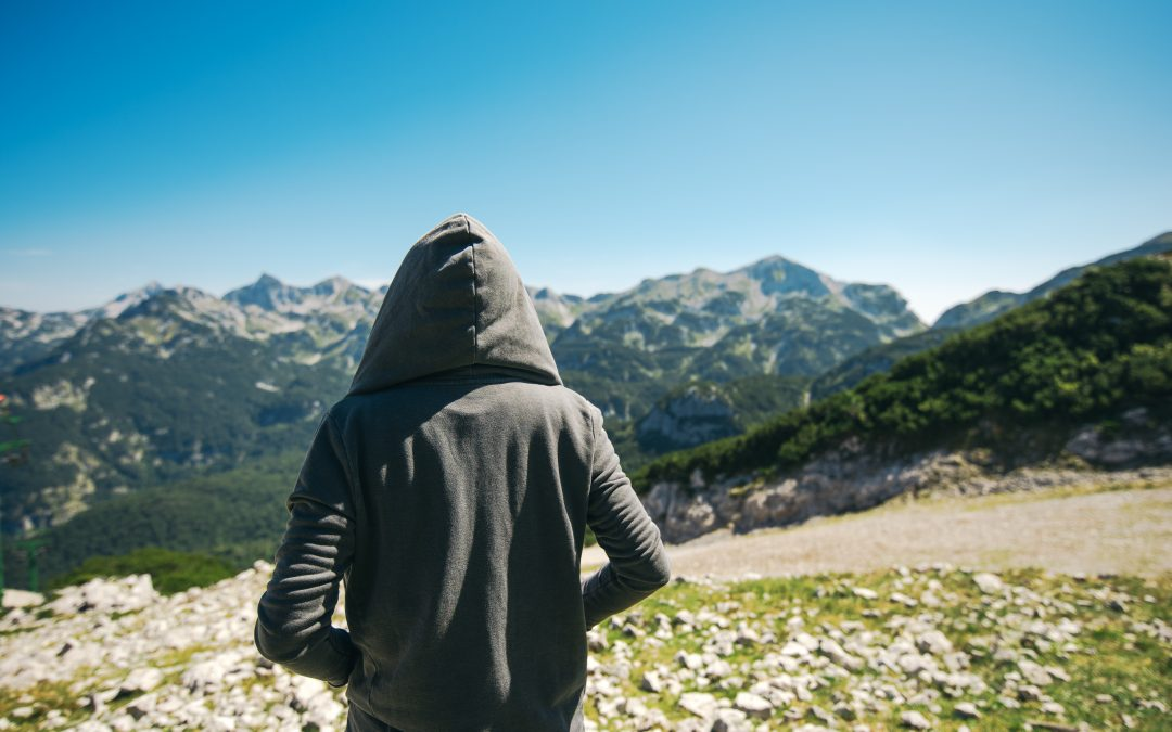 mountain hiker with hoodie up facing mountains